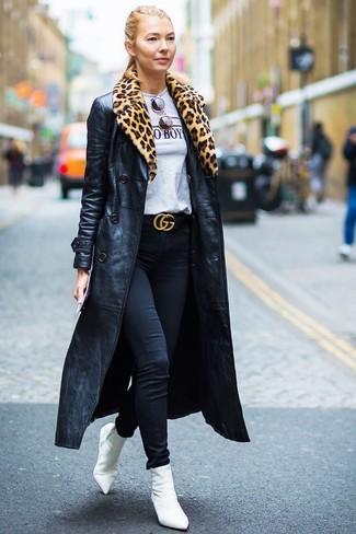 Cómo combinar: gabardina de cuero negra, camiseta con cuello circular estampada gris, vaqueros pitillo negros, botines de elástico blancos