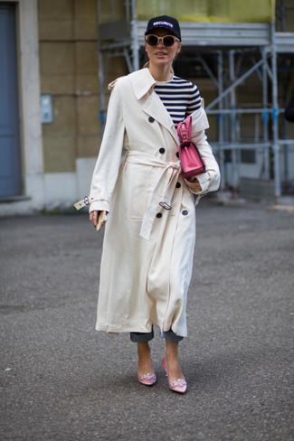 Cómo combinar: gabardina blanca, camiseta de manga larga de rayas horizontales en blanco y negro, vaqueros azules, zapatos de tacón de satén con adornos rosados