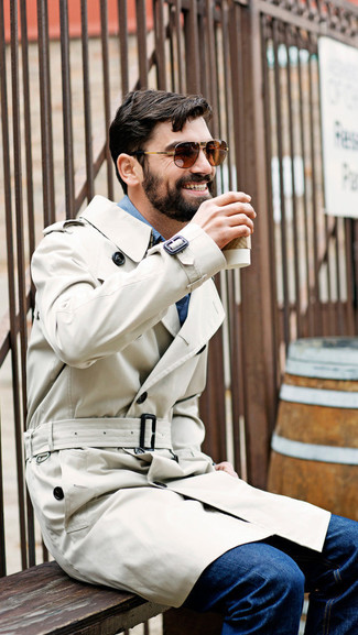 Cómo combinar: gabardina en beige, camisa de manga larga de cambray azul, vaqueros azul marino, gafas de sol marrónes