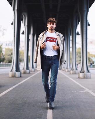 Cómo combinar: gabardina en beige, camiseta con cuello circular estampada en blanco y rojo, vaqueros azul marino, botines chelsea de cuero negros