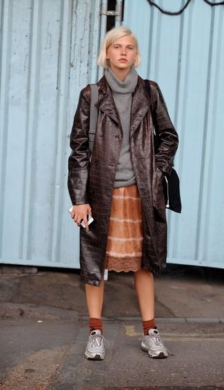 Cómo combinar: gabardina de cuero en marrón oscuro, jersey con cuello vuelto holgado gris, vestido camisola efecto teñido anudado naranja, deportivas plateadas