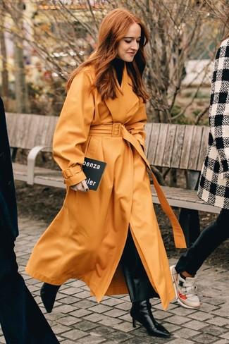Cómo combinar: gabardina de cuero naranja, jersey de cuello alto negro, pantalones anchos de cuero negros, botines de cuero negros