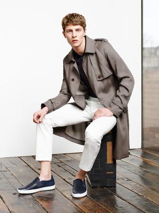 Cómo combinar: gabardina marrón, camisa polo estampada azul marino, pantalón de vestir blanco, zapatillas slip-on de cuero azul marino