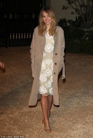 Look de Suki Waterhouse: Gabardina marrón, Vestido midi de encaje blanco, Botines de cuero con recorte marrón claro