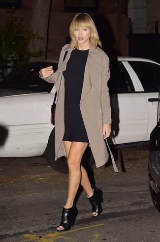 Look de Taylor Swift: Gabardina marrón, Vestido recto negro, Botines de cuero con recorte negros, Bolso bandolera de cuero negro