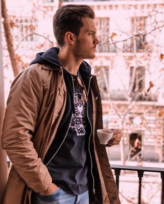 Cómo combinar: gabardina marrón, sudadera con capucha negra, camiseta con cuello circular estampada negra, vaqueros azules