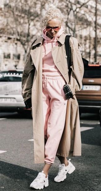Cómo combinar: gabardina en beige, sudadera con capucha rosada, pantalón de chándal rosado, deportivas blancas