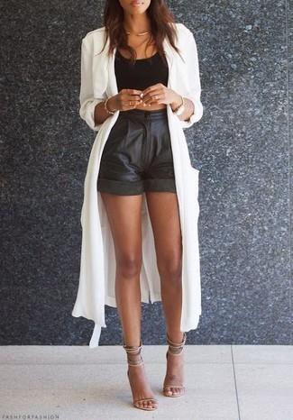 Cómo combinar: gabardina ligera blanca, top corto negro, pantalones cortos de cuero negros, sandalias de tacón de cuero en beige