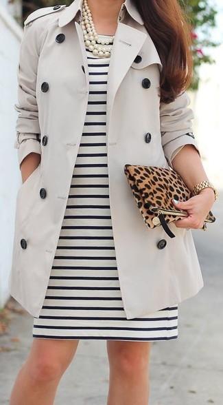 Empareja una gabardina beige con un vestido tubo de rayas horizontales negro y blanco para después del trabajo.