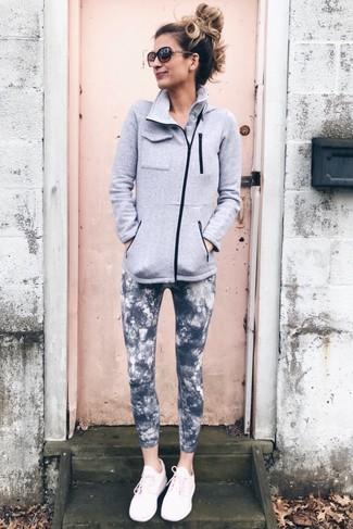 Cómo combinar: jersey con cremallera de forro polar gris, leggings efecto teñido anudado en gris oscuro, deportivas rosadas, gafas de sol en marrón oscuro