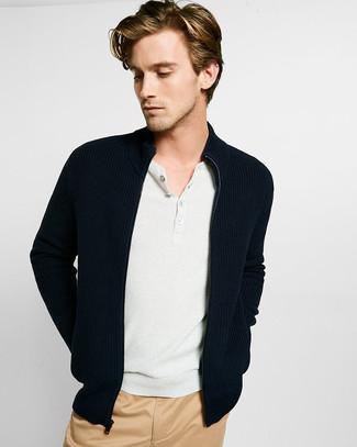 Cómo combinar: jersey con cremallera negro, camiseta henley blanca, pantalón chino marrón claro