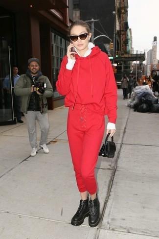 Cómo combinar: jersey con cremallera blanco, sudadera con capucha roja, pantalón de chándal rojo, botas planas con cordones de cuero gruesas negras