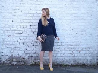 Elige un jersey con cuello circular azul marino y una falda lápiz gris oscuro para conseguir una apariencia glamurosa y elegante. Dale un toque de elegancia a tu atuendo con un par de zapatos de tacón de cuero amarillos.