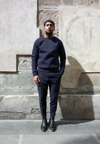 Cómo combinar: jersey con cuello circular azul marino, pantalón de vestir de lana azul marino, botas casual de cuero negras, gorro negro