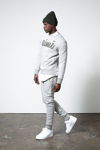 Cómo combinar: jersey con cuello circular estampado gris, camisa de manga larga blanca, pantalón de chándal gris, tenis blancos