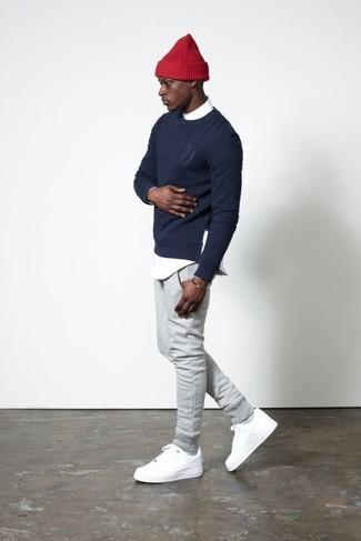Cómo combinar: jersey con cuello circular estampado azul marino, camisa de manga larga blanca, pantalón de chándal gris, tenis blancos