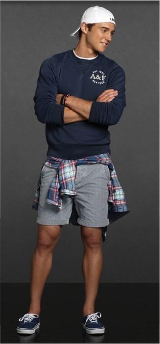 Cómo combinar: jersey con cuello circular azul marino, camisa de manga larga de tartán azul, pantalones cortos grises, tenis azul marino