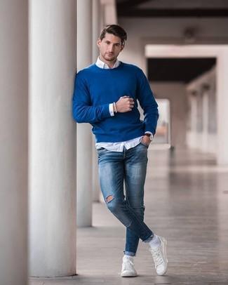 Cómo combinar: jersey con cuello circular azul, camisa de manga larga blanca, vaqueros pitillo desgastados azules, tenis de cuero blancos