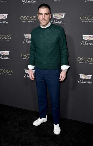 Cómo combinar: jersey con cuello circular verde oscuro, camisa de vestir blanca, pantalón chino azul marino, tenis blancos