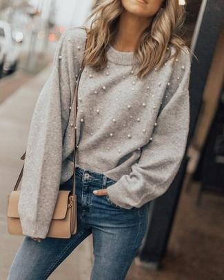 Cómo combinar: jersey con cuello circular con adornos gris, vaqueros pitillo azules, bolso bandolera de cuero marrón claro