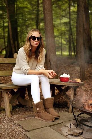 Cómo combinar: jersey con cuello circular en beige, vaqueros pitillo blancos, botas ugg marrónes, gafas de sol en marrón oscuro
