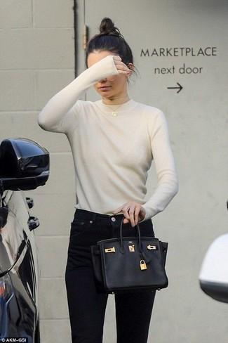 Cómo combinar: jersey con cuello circular en beige, vaqueros pitillo negros, bolso de hombre de cuero negro