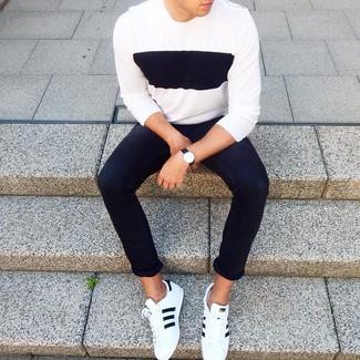 Cómo combinar: jersey con cuello circular en blanco y negro, vaqueros pitillo negros, tenis de cuero en blanco y negro, reloj de cuero negro
