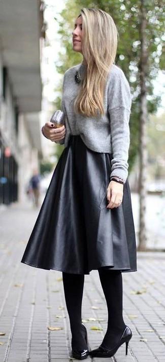 Look de moda: Jersey con cuello circular gris, Falda midi de cuero plisada negra, Zapatos de tacón de cuero negros, Cartera sobre de cuero plateada