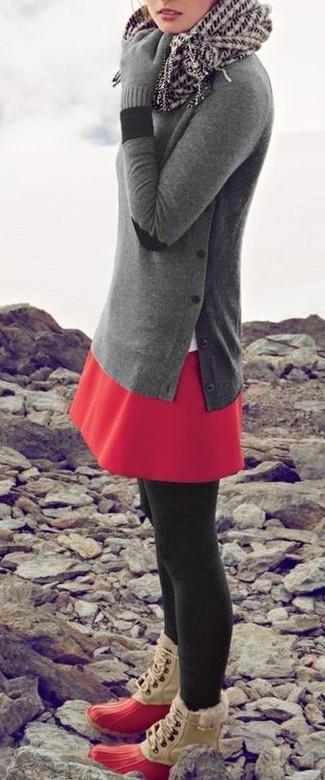 Cómo combinar: jersey con cuello circular gris, falda skater roja, botas para la nieve rojas, bufanda estampada en blanco y negro
