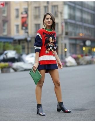 Cómo combinar: jersey con cuello circular estampado rojo, falda skater azul marino, botines chelsea de cuero negros, cartera sobre de cuero verde