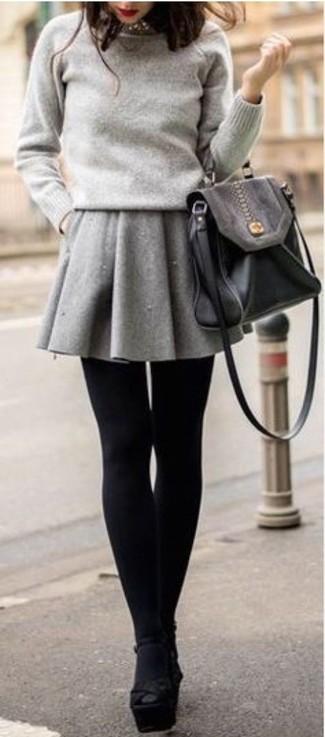 Cómo combinar: jersey con cuello circular gris, falda skater gris, sandalias de tacón de ante gruesas negras, bolso de hombre de cuero negro