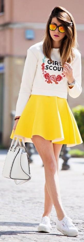 Cómo combinar: jersey con cuello circular estampado blanco, falda skater amarilla, zapatillas plimsoll blancas, bolso de hombre de cuero blanco