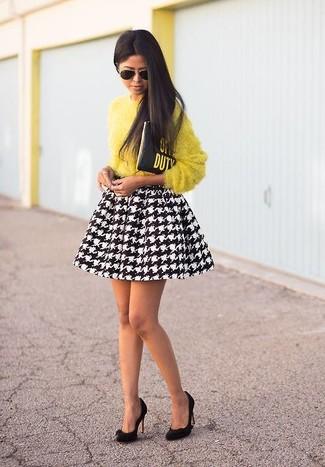 Cómo combinar: jersey con cuello circular de angora amarillo, falda skater de pata de gallo en negro y blanco, zapatos de tacón de ante negros, cartera sobre de cuero estampada negra