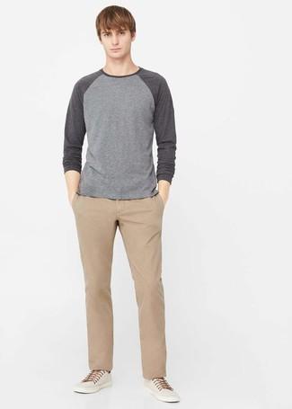 Cómo combinar: jersey con cuello circular gris, pantalón chino marrón claro, zapatillas plimsoll en beige