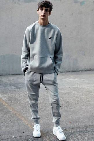 Cómo combinar: jersey con cuello circular gris, pantalón de chándal gris, tenis blancos