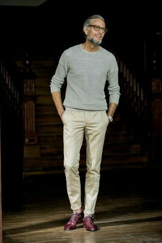 Cómo combinar: jersey con cuello circular gris, pantalón de vestir en beige, zapatos derby de cuero burdeos, reloj plateado
