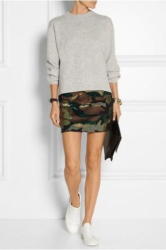 Cómo combinar: jersey con cuello circular gris, minifalda de camuflaje verde oliva, zapatillas plimsoll blancas, cartera sobre de cuero en marrón oscuro