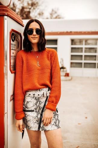 Look de moda: Jersey con cuello circular naranja, Minifalda de cuero con print de serpiente gris, Gafas de sol en negro y dorado, Colgante dorado