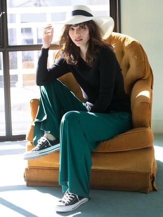 Cómo combinar: jersey con cuello circular negro, pantalones anchos verde oscuro, tenis de lona en negro y blanco, sombrero de paja blanco
