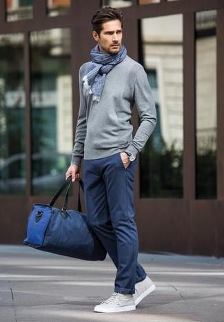 Cómo combinar: jersey con cuello circular gris, pantalón chino azul marino, tenis de cuero grises, bolsa de viaje de lona azul marino