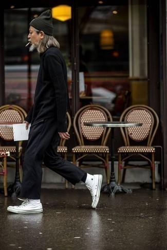 Moda para hombres de 50 años: Opta por un jersey con cuello circular negro y un pantalón chino negro para lidiar sin esfuerzo con lo que sea que te traiga el día. Zapatillas altas de lona blancas añaden un toque de personalidad al look.