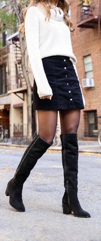 Cómo combinar: jersey con cuello vuelto holgado blanco, falda con botones vaquera negra, botas sobre la rodilla de ante negras