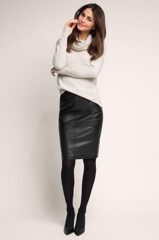 Cómo combinar: jersey con cuello vuelto holgado gris, falda lápiz de cuero negra, zapatos de tacón de cuero negros, medias negras