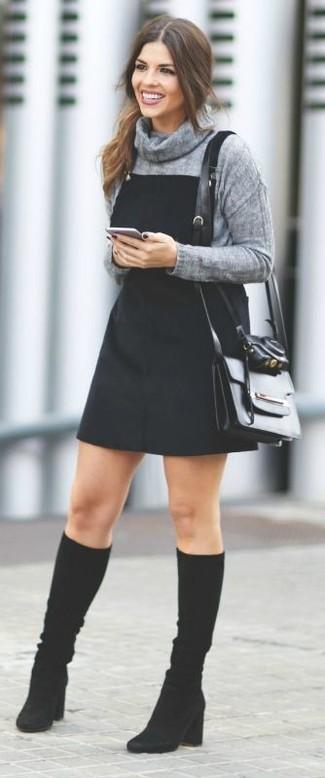 Cómo combinar un jersey con cuello vuelto holgado gris: Considera emparejar un jersey con cuello vuelto holgado gris con un pichi vaquero negro para un look agradable de fin de semana. Con el calzado, sé más clásico y elige un par de botas de caña alta de ante negras.