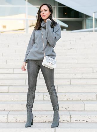 Cómo combinar: jersey con cuello vuelto holgado gris, vaqueros pitillo en gris oscuro, botines chelsea de ante grises, bolso bandolera de cuero con adornos blanco