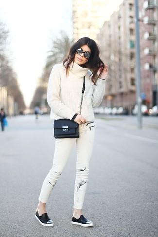 Cómo combinar: jersey con cuello vuelto holgado blanco, vaqueros pitillo estampados blancos, zapatillas slip-on de cuero negras, bolso bandolera de cuero negro