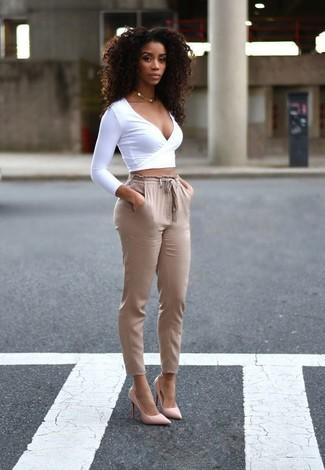 Cómo combinar: jersey corto blanco, pantalón de pinzas marrón claro, zapatos de tacón de cuero rosados, collar dorado