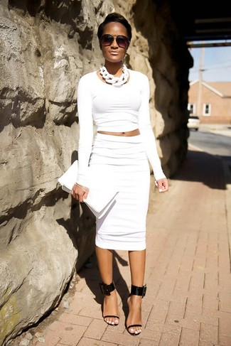 Cómo combinar: jersey corto blanco, falda lápiz blanca, sandalias de tacón de cuero negras, cartera sobre de cuero blanca