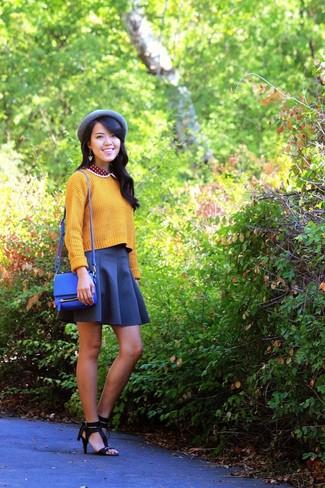 Cómo combinar: jersey corto de punto amarillo, falda skater azul marino, sandalias de tacón de cuero negras, bolso bandolera de cuero azul