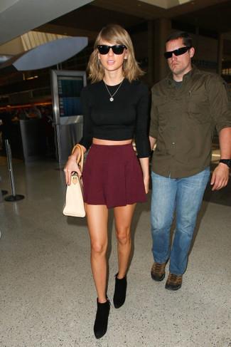Look de Taylor Swift: Jersey Corto Negro, Falda Skater Burdeos, Botines de Ante Negros, Bolsa Tote de Cuero en Beige